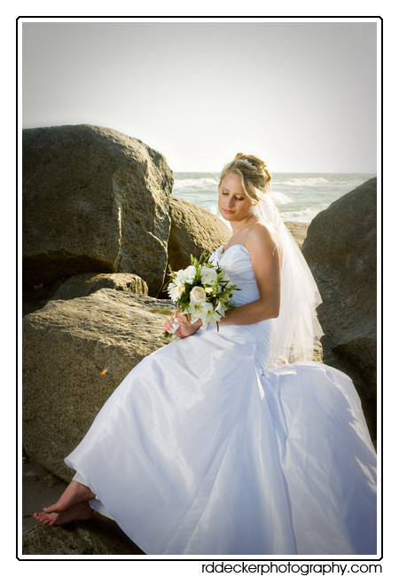 Bride poses for a portrait on a rock jetty along North Carolina's Crystal Coast
