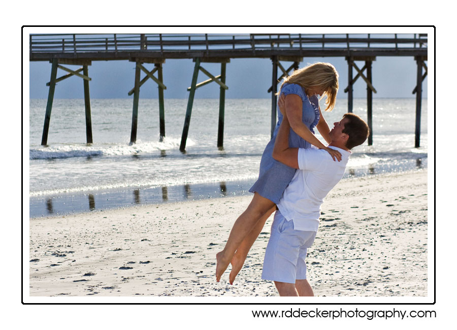 Love on the beach with a fishing pier in the background.